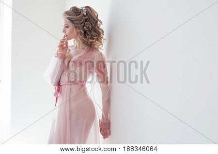 pretty girl in Pink Lingerie stands at white walls hairstyle bride boudoir