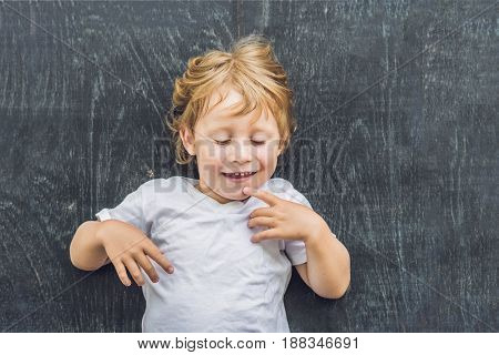Top View Of A Little Blond Kid Boy With Space For Text And Symbols On The Old Wooden Background. Con