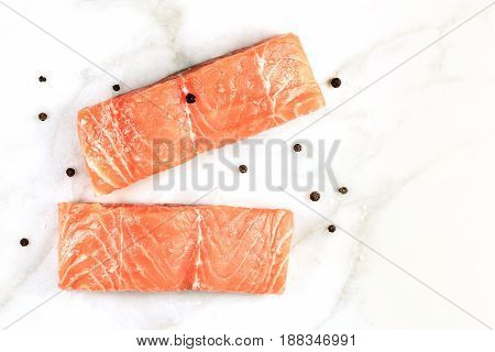 An overhead photo of two slices of salmon on a white marble table with copy space, with salt and pepper