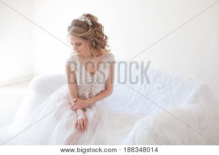 beautiful girl in lingerie sitting on a white couch before the wedding