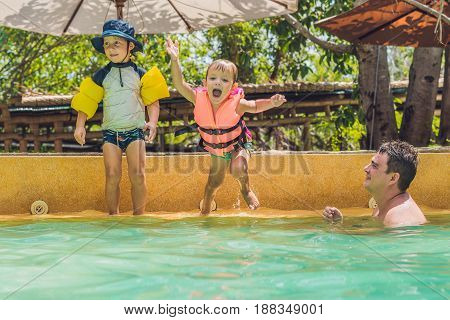 two young boys friends jumping in the pool.
