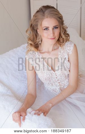beautiful bride sitting on a white couch in lingerie wedding