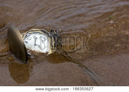 pocket watches round on the sand under the water time