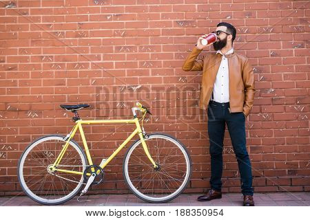 Young Stylish Man With A Beard Sitting On A Brick Background Bicycle And Drinking Coffee
