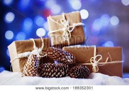 Handmade gift boxes from craft paper over snowy wooden table in blue light