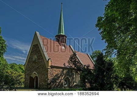The photo shows an old brick church. The construction of the walls is made of stone. The roof is covered with a red tile. In the middle of the roof is a small bell tower. There are small windows in the walls. A wooden two-door door leads into the interior