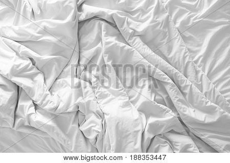 Top view of unmade bedding blanket or white fabric wrinkle texture background