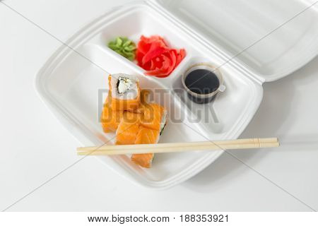 Roll With Chopsticks, Rolls, Sushi. Chopsticks, Ginger, Soy Sauce In Container Delivery