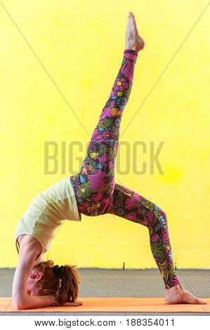 Full length picture of flexible woman practicing advanced yoga. Female working out against yellow wall in class. Body balance training. Fitness and healthy lifestyle concept.