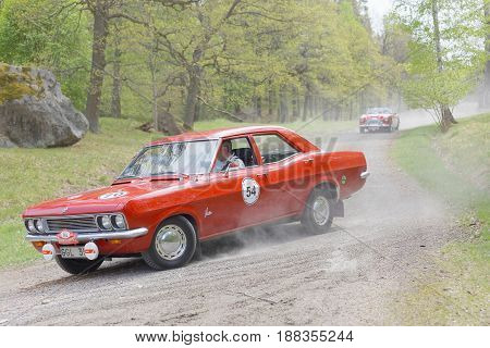 STOCKHOLM SWEDEN - MAY 22 2017: Red Vauxhall Victor 943696 classic car from 1970 driving on a country road in the public race Gardesloppet in the forests at Djurgarden Stockholm Sweden. May 22 2017