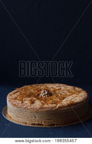 homemade walnut pie cake on a black background