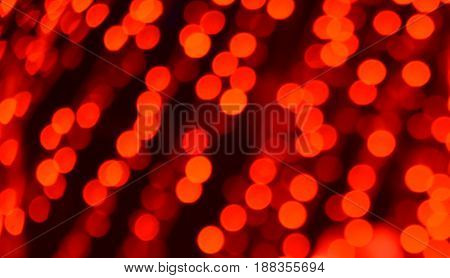 Defocused Bokeh twinkling lights background. Festive background with natural bokeh and bright red defocused lights.