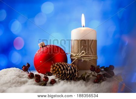 Candle and christmas decoration in snow with blue light background