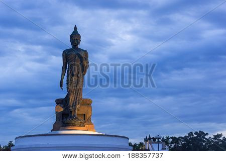 Big Buddha statue on sunset sky background.