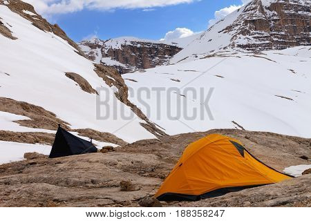 Two Camping Tents On Rocks In Snow Mountains At Evening