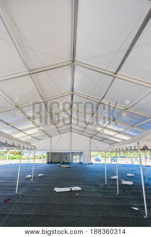 Inside of a large white tent in a grass field for parties and entertaining
