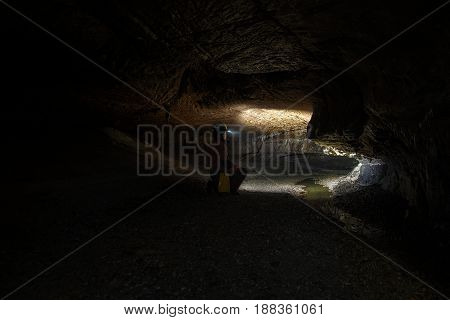 Woman with headlamp inside dark cave closeup