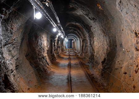 Underground mine passage with rails and light