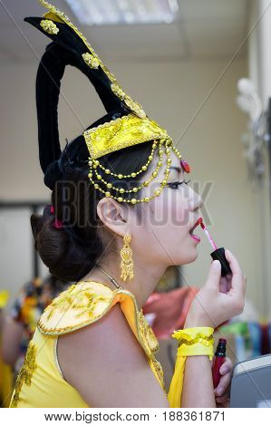 beautiful asian actress in yellow stage costume makes up her lips