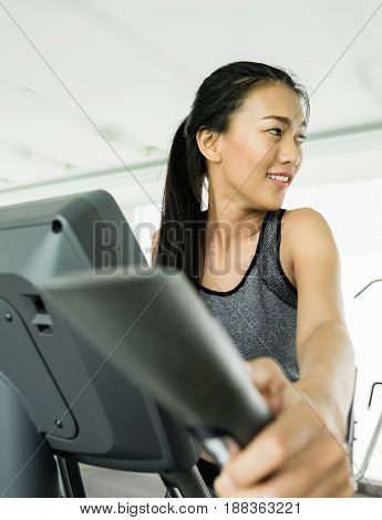 Asian woman exercising on Elliptical trainer machine at the gym.