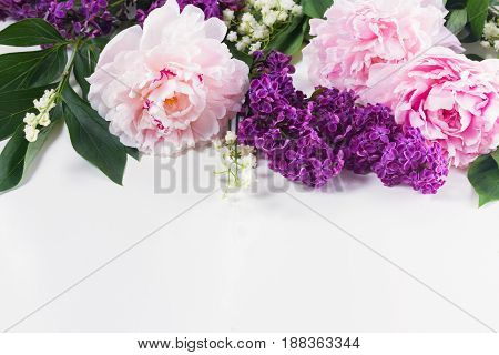 Floral borders of fresh flowers - lilac, peonies and lilly of the walley flowers on white background