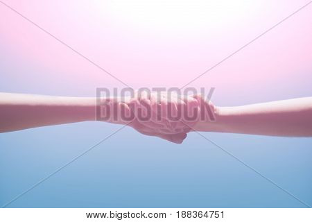 hands of women or girls holding strong together on bright light blue background. Grasp. Handshake. Help care and support. Family and friendship
