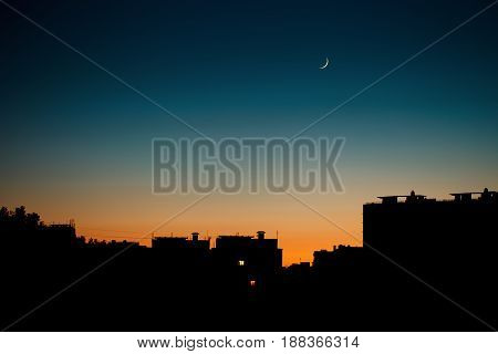A warm summer evening in the city. Cityscape silhouette with the moon.