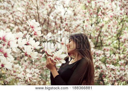 Girl With Long, Brunette Hair Enjoying Magnolia Flower Blossom