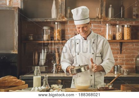 Bakery chef cooking bake in the kitchen professional sift the flour
