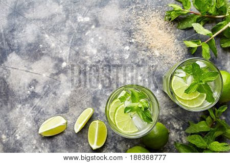 Mojito cocktail traditional Cuban alcohol drink top view copy space in highball glass, summer tropical vacation beverage with rum, mint leaves, lime citrus juice, soda water and ice on concrete table.