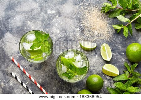 Mojito cocktail Cuban alcohol drink top view copy space in highball glass, summer tropical vacation beverage with rum, citrus slice, spearmint leaves, lime juice, soda water and ice on concrete table.