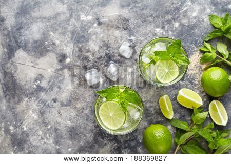 Mojito cocktail alcohol bar summer refreshment drink traditional Cuba beverage top view copy space two highball glass, with rum, citrus slice, mint, lime, soda water and ice on concrete table.
