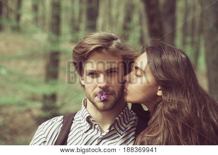 boyfriend and girlfriend with blue flowers in mouths. Pretty girl or cute woman with closed eyes kissing handsome man on cheek bearded face on natural background. Couple in love. Flirting sensuality