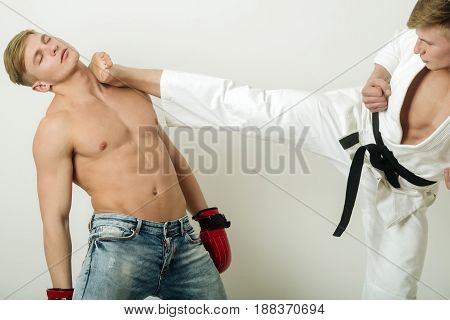 Fit Karateka In Kimono Leg Kicking Head Of Boxer