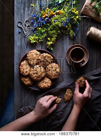 Oatmeal cookies from whole wheat flour on a wooden table in rustic style. Female hands hold a cookie and a cup of tea. A bouquet of wildflowers on the table. Summer mood. Flat lay.