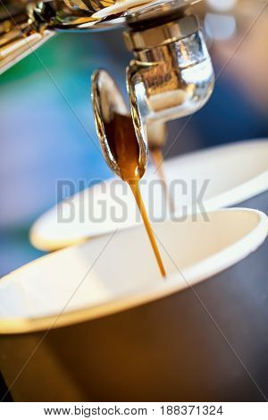 Close-up fresh espresso pours in disposable cup, Italian espresso machine. Coffee culture and professional coffee making, coffe to go, service, catering concepts