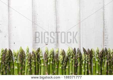 Fresh green asparagus in a row on white wooden background, copyspace