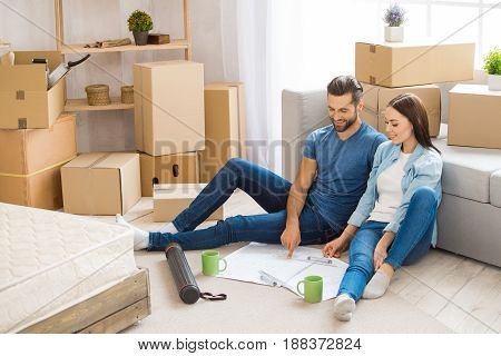 Young couple man and woman moving to a new apartment together relocation planning interior