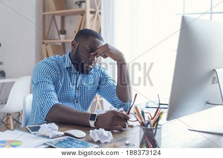 Young african male working in the office business stressed