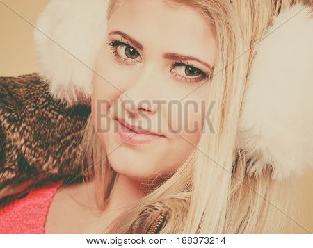 Accessories and clothes for cold days fashion concept. Blonde woman in winter warm earmuffs and jacket.