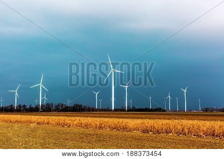 Windmills for electric power production on the background of a stormy sky. Windmill generator turbines.
