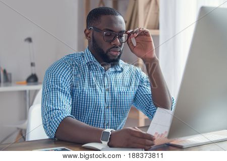 Young african male working in the office business data analysis