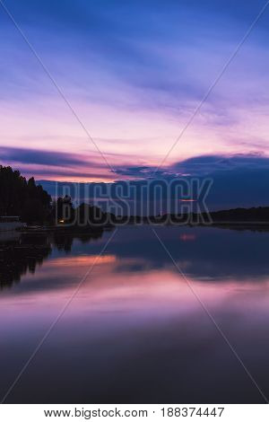 Scenery after sunset at the river in dusk colorful dramatic evening sky reflected in the water Khmelnytskyi Ukraine.