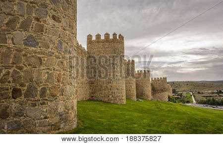Walls of the historic city of Avila, at the blue hour, in Spain. the old city of Avila and its extramural churches were declared a World Heritage site by UNESCO