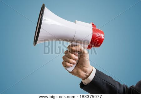 Announcement concept. Hand holds megaphone on blue background.
