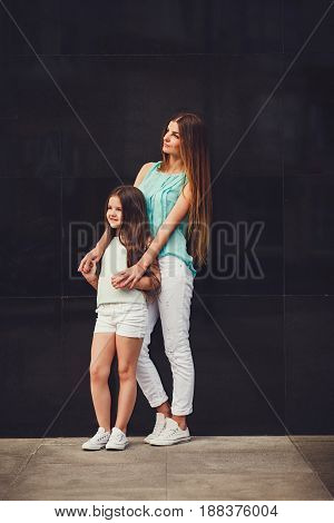 Young beautiful mom with her daughter wearing t-shirt and jeans posing against wall in city