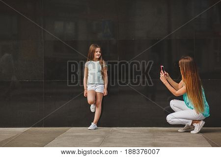 Happy mother taking portrait child on smartphone in city family wearing a t-shirts and white shorts