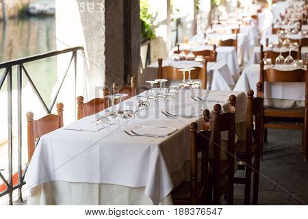 table setting for a lovey dinner. Empty glasses set in restaurant. Part of interior. napkins, plates, and eating utensils