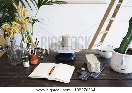 Pieces of grey raw clay on marble board and pottery sculpting wheel prepared for modeling ceramic pots on wooden dark brown table with notebook dried flowers tools and cactus in cute pot with face