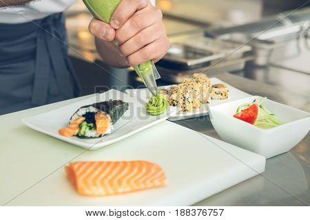 Male japanese restaurant chef cooking in the kitchen adding wasabi